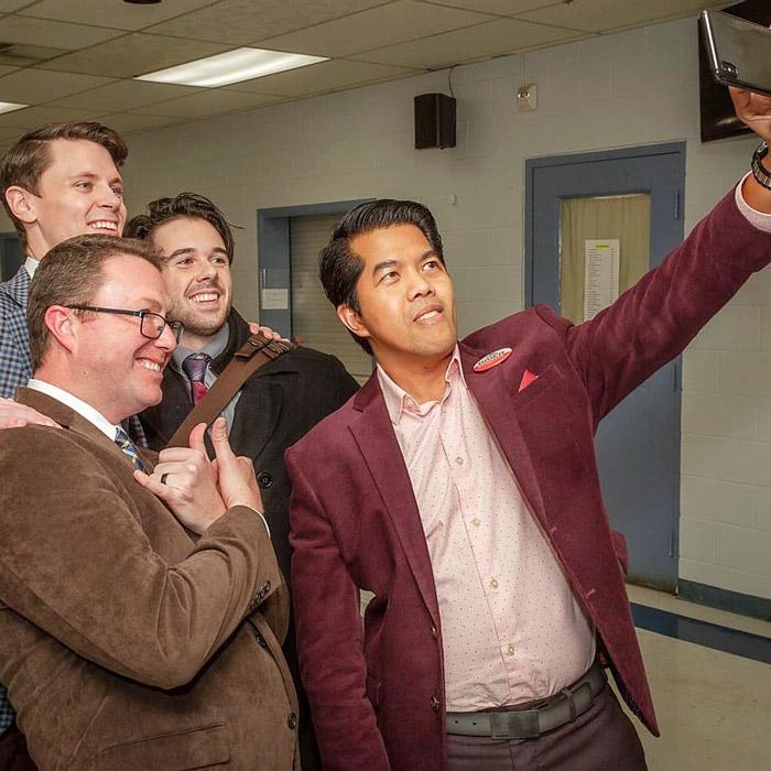 Four men taking a selfie.