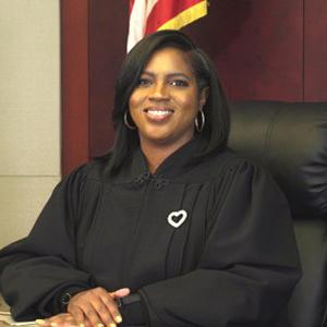 Woman sitting at judge bench, wearing black robe.